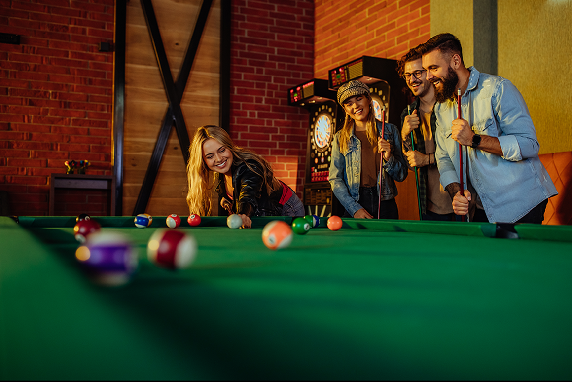 Group of young friends playing billiards