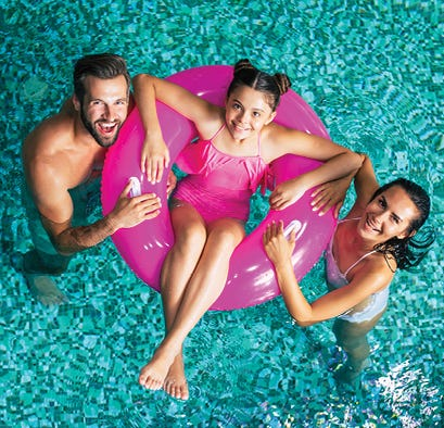 Family in pool with daughter floating on a tube