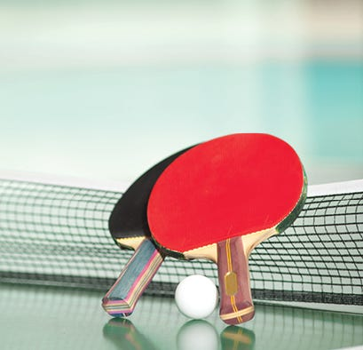 Ping pong paddles on a ping pong table leaning on net