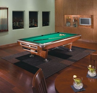 Pool table with billiard balls, pool cue in apartment