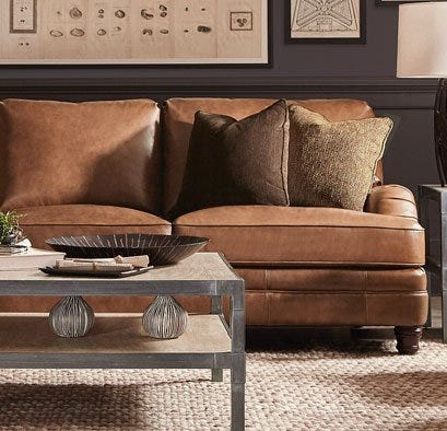 Brown leather sectional with coffee table and jute rug