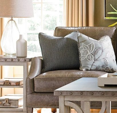 Grey leather sofa with pillows, end table and lamp