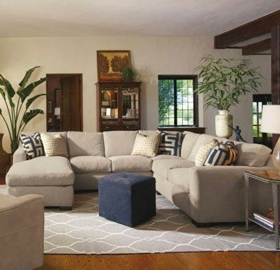 Beige cloth sectional with blue ottoman and grey rug