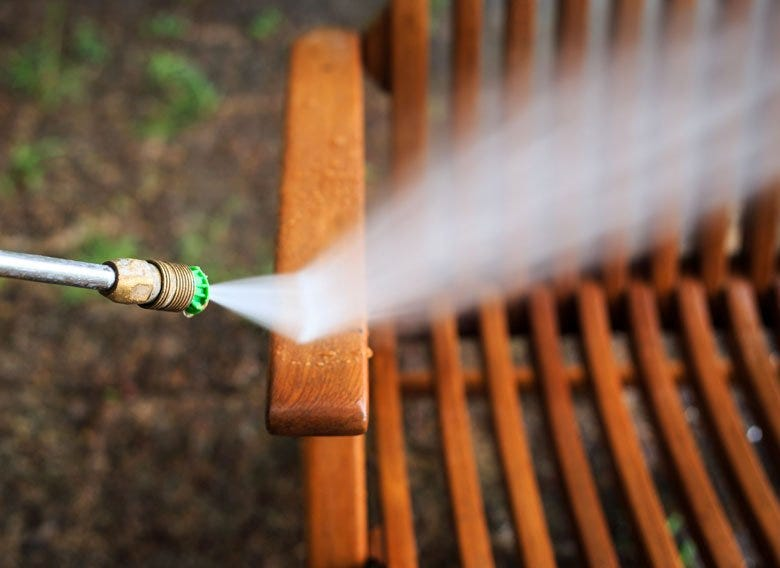 Power washer spraying off wooden patio furniture