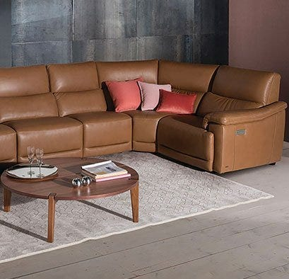 Brown leather sectional with coffee table and grey rug