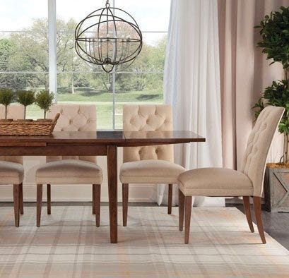 Mid century modern wood table with cream fabric dining chairs and orbital chandelier
