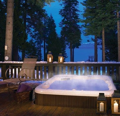 Spa in built-in deck with snow and candles around the rim
