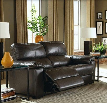 Brown leather reclining sofa in living room with end tables and lamps