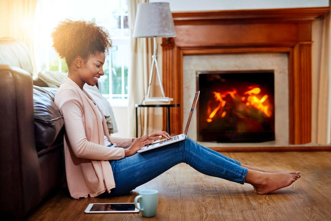 Young woman on laptop in front of fireplace