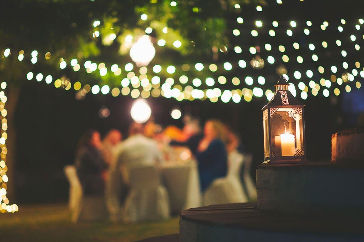 Outdoor dining table beneath string lights