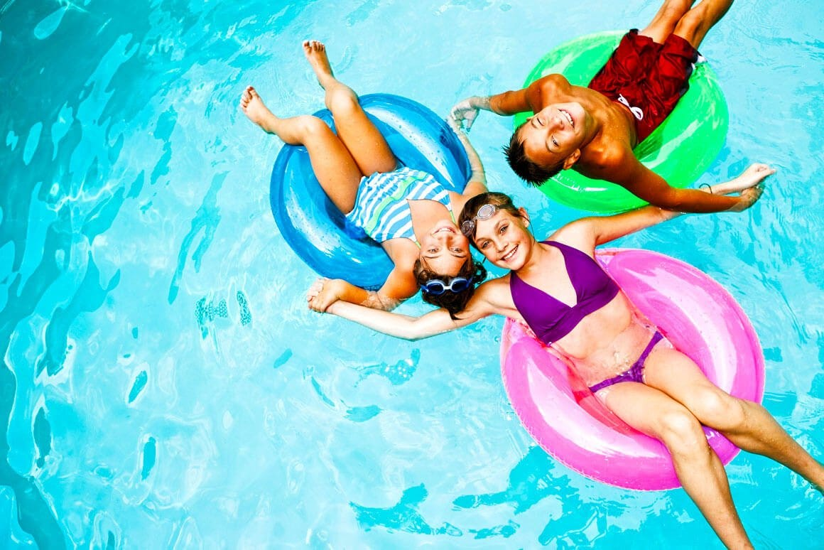 Children floating in pool floats
