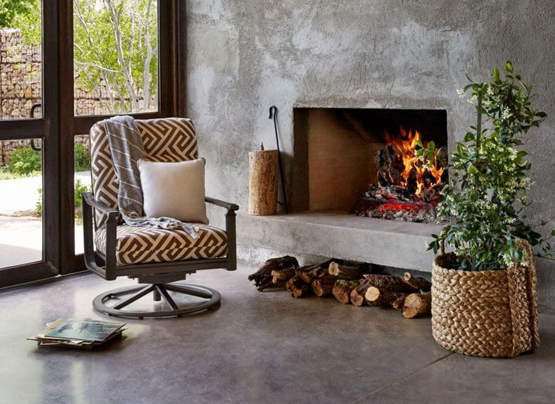 Patio chair in sunroom beside fireplace and plant