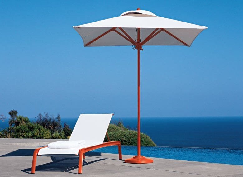 Patio umbrella beside lounge chair at poolside