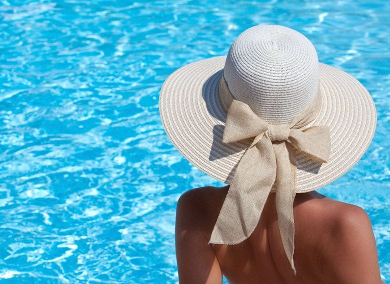 Woman wearing a hat beside a pool